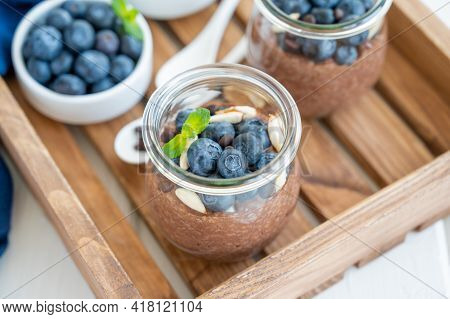 Chocolate Chia Pudding With Blueberry, Almonds And Mint On Top In A Glass Jar On A White Wooden Back