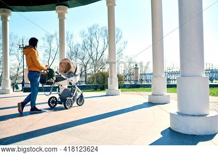 A Young Mother Walks With A Stroller And A Child On The Street To The Park And Drinks Coffee. Lookin