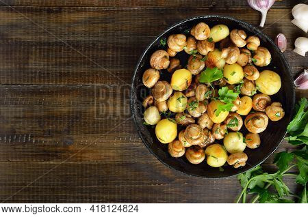 Delicious Fried Mushrooms And Potatoes In Frying Pan On Wooden Background With Copy Space. Top View,