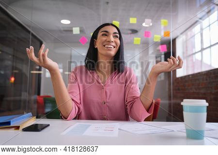 Happy mixed race businesswoman sitting at desk while having a video call smiling. independent creative design business.