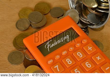 Stack Of Coins And Calculator Written With Fundraising. Financial Concept.