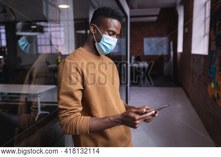 African american businessman wearing face mask standing in corridor looking at tablet. independent creative design business during covid 19 coronavirus pandemic.