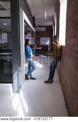 Diverse male and female colleagues at work standing discussing in corridor. independent creative design business.