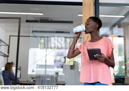 African american businesswoman standing at corridor drinking coffee using digital tablet. business person in a modern office.