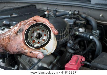 Un mecánico de automóviles muestra un filtro de aceite sucio, viejo ha quitado de un coche durante el mantenimiento general