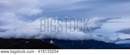 Panoramic View Of Puffy Clouds Over The Canadian Mountain Landscape. Colorful Winter Sunset Cloudsca