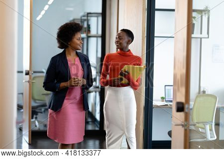 Happy african american female business colleagues walking through corridor holding documents talking. business in a modern office.