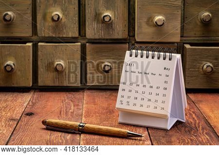 May 2021 - spiral desktop calendar on a weathered barn wood table with rustic apothecary drawers in background and a stylish pen, time and business concept