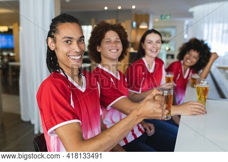 Diverse group of male and female sports fans having beer watching game at bar. sports fan friends socialising and drinking at bar.