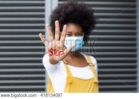 Portrait of mixed race woman wearing face mask making stop gesture with hand covered in writing. equal rights and justice protestors on demonstration march during coronavirus covid 19 pandemic. .