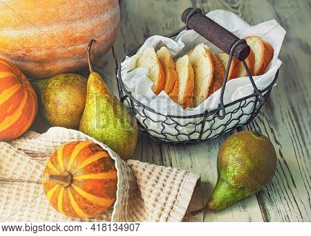 Vintage Basket With Bread, Pumpkins And Pears On Wooden Background, Toned.