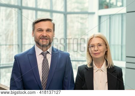 Portrait of smiling mature business people in formalwear standing against tall panoramic window of modern office
