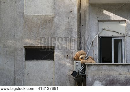 A Teddy Bear Left In A Balcony Of An Old Neglected Building.