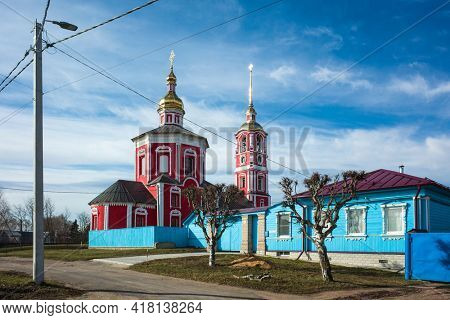Suzdal, Russia - 19 april, 2021: Street of Suzdal, Wooden traditional house, Church of holy princes Boris and Gleb (Borisoglebskaya) in spring middle april, Russian architecture, Golden Ring of Russia