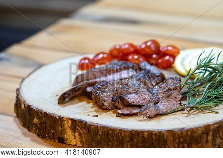 Steak Slice On The Wood Plate, Decoration By Lemon Slice, Tomato, And Rosemary On The Wood Table In