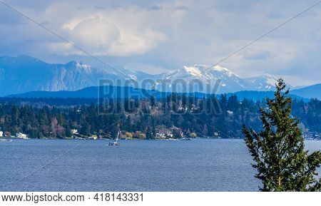 A View Of The Shoreline Of Bellevue, Washington With The Cascade Mountains Behind.