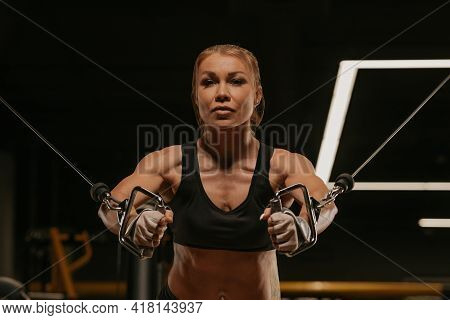 A Close-up Photo Of A Fit Woman With Blonde Hair Who Is Doing A Chest Workout On The Cable Machine I