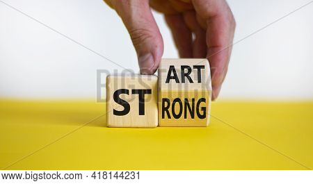 Start Strong Symbol. Businessman Turns Wooden Cubes With Words 'start Strong'. Beautiful Yellow Tabl