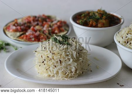 Indian Dish Made Of Basmati Rice Flavoured With Cumin Seeds And Spices. Served With Bottle Gourd Cur