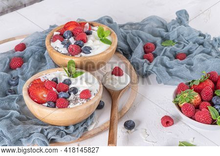 Yogurt And Berries For Healthy Breakfast. Bowl Of Greek Yogurt With Raspberry, Blueberries And Straw