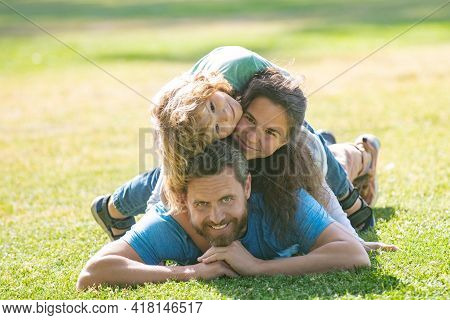 Happy Young Family Hugging And Embracing Together Outside In Green Nature.