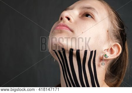 Closeup Face Of Young Caucasian Teenager Girl With Black Kinesiology Tape Placed On The Neck On Dark