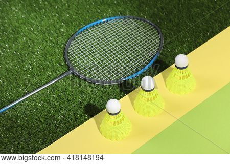 Shuttlecocks And Racquet On Green Court Combined With Color Paper Background. Badminton Equipment