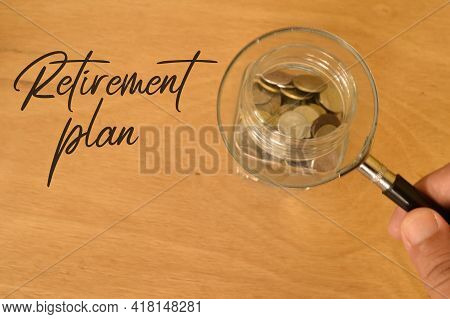 Phrase Retirement Plan Written On Board With Coins And Magnifying Glass