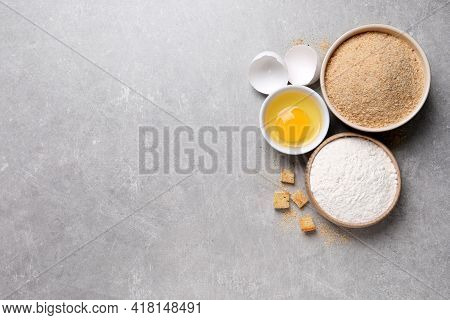 Fresh Breadcrumbs, Flour And Egg On Light Grey Table, Flat Lay. Space For Text