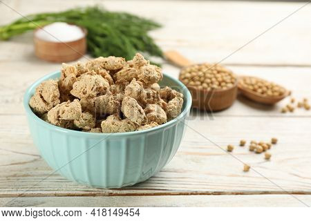 Dehydrated Soy Meat Chunks In Bowl On White Wooden Table. Space For Text