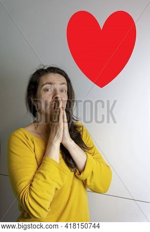 A White Beautiful Young Woman Holds Her Folded Hands In A Sign Of Hope. Prays, Hopes, Wishes, Pleads