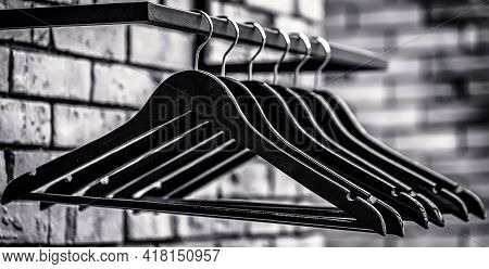 Fashionable Different Types Of Hanger. Wooden Coat Hanger Clothes. Many Wooden Black Hangers On A Ro