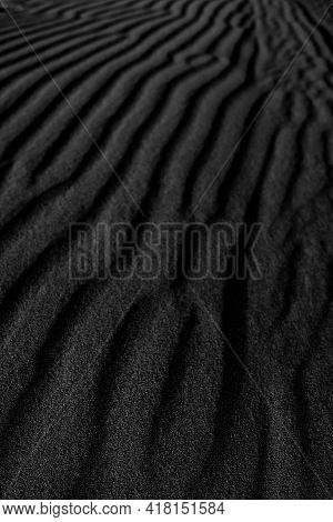 Black Sand Dune. Black Sand Beach Macro Photography. Background, Texture, Wave Pattern Of Oceanic Sa