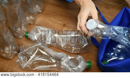 Waste Sorting And Recycling Concept. Hands Put Crushed Plastic Bottles Into Blue Eco Bag. Preparatio