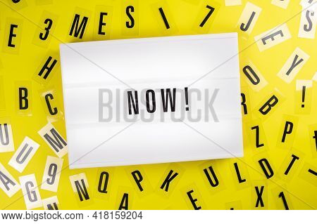 Lightbox With Text Now On Yellow Background With Black Letters Randomly Scattered. Concept Of Motiva