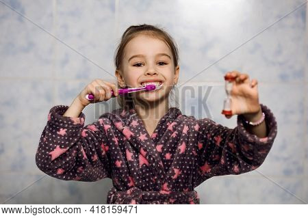Little Cheerful Girl Brushes Her Teeth With Toothpaste With An Hourglass Timer. Parents Teach Their