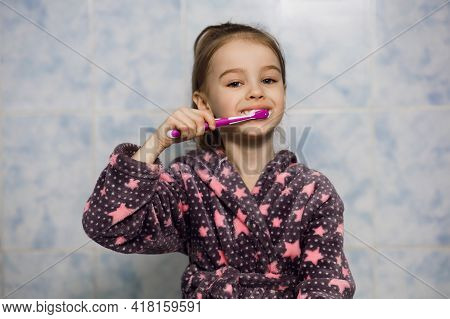Little Cheerful Girl Brushes Her Teeth With Toothpaste. Parents Teach Their Child To Care For Their