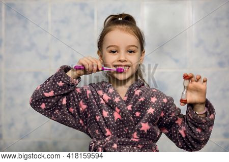 Little Girl Brushes Her Teeth With Toothpaste With An Hourglass Timer. From Childhood, Parents Teach