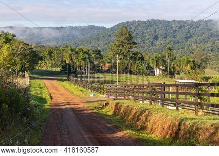 Farm Road With Field, Mountains And Forest In Background, Ivoti, Rio Grade Do Sul, Brazil
