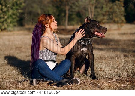 An Informal Redhead Woman With Pigtails Walks A Black Pit Bull. Dangerous Fighting Dog Breed Adores