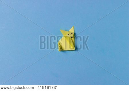 An Origami Fox Is Folded From Yellow Paper In The Technique Of Origami With Painted Eyes, Nose. In T