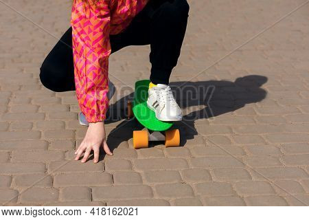 A Teenager Is Riding A Skateboard Or Penny Board In The Park. The Child Is Dressed In Bright Clothes