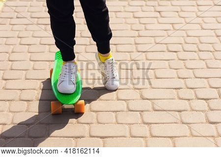 Skateboarding Or Penny Board Concept. Close Up View Of Legs And Bright Green Penny Board. Free Space