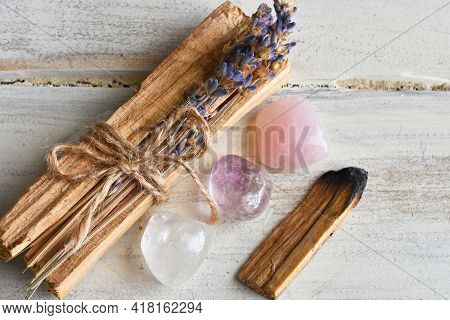 A Close Up Image Of Holy Wood Incense Sticks With Healing Rose Quartz And Amethyst Crystals.