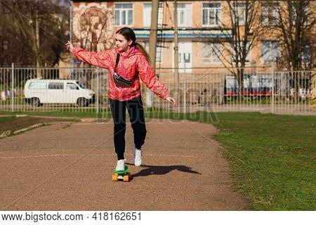 Teenage Girl In Bright Clothes Ride A Skateboard Or Pennyboard In The Park. Skateboarding Is A Great