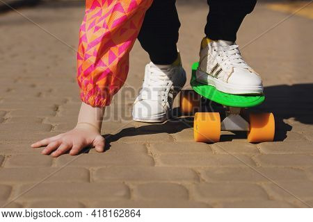 A Stubborn Child Learns To Ride A Green Skateboard Or Pennyboard In The Park. An Active Teenager Rid