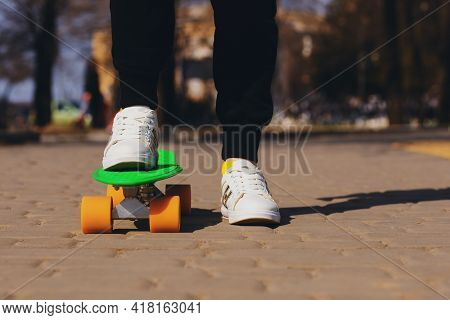 The Child Is Riding A Green Skateboard Or Penny Board. The Teenager Is Fond Of Skateboarding. The He