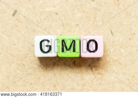 Color Alphabet Letter Block In Word Gmo (abbreviation Of Genetically Modified Organisms) On Wood Bac
