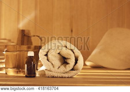 Wooden Bath Accessories With A Bottle Of Aromatic Bath Oil, A Towel In The Sauna And A Hat In The Ba