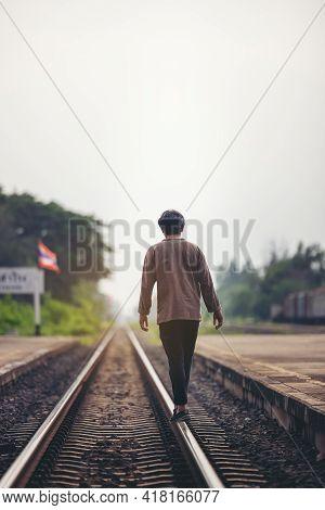 Man Walk Away On Railroad With Warm Light. Selective Focus. Traveler Man On Railroad.